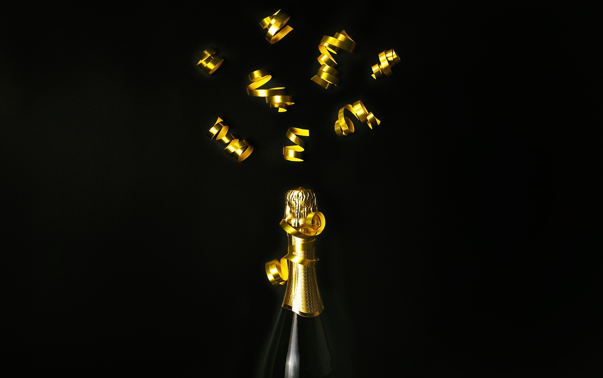 Champagne bottle with golden party streamers on black background. Celebration concept. Flat lay style. Copy space.
